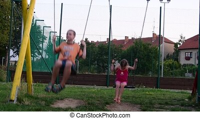 View of boy and girl on the swing set