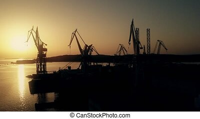 Scenic aerial view of the shipyard cranes and the sea...