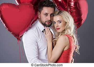 Portrait of couple holding heartshape balloons
