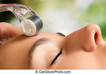 Beauty treatment with skin derma roller. - Macro close up...