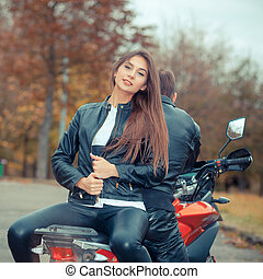 Pretty girl with a biker posing near a sports bike. Beautiful couple with a motorcycle at sunset
