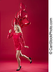 Running woman with red heartshape balloons