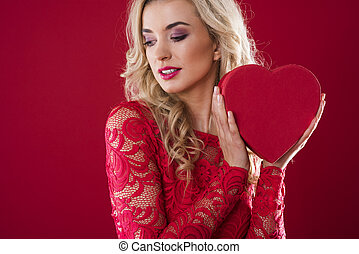 Woman holding heartshape box next to her face