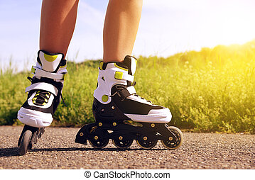 Female legs in inline skates in action outdoors on sunny...