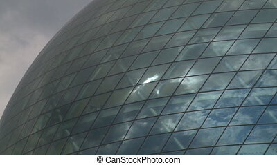 Clouds and sun reflections on modern sphere glass building....