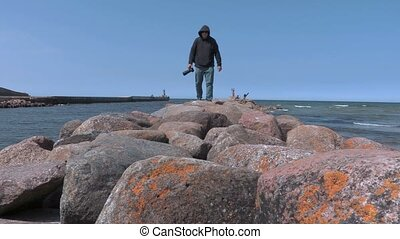 Photographer traveler walking alone on the stone pier by the sea