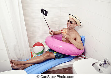 man with swim ring taking selfie in the bathroom - a young...