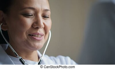 Positive female doctor using the stethoscope