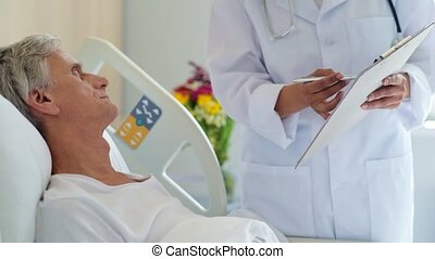 Senior ill men signing papers in a hospital - Sign here....