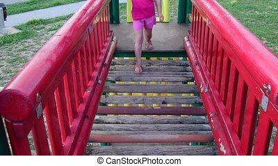 View of girl goes on rope bridge in the playset at...