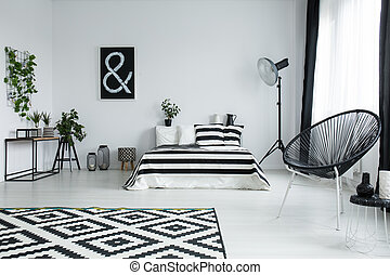 Striped coverlet on bed in stylish bedroom - Patterned black...