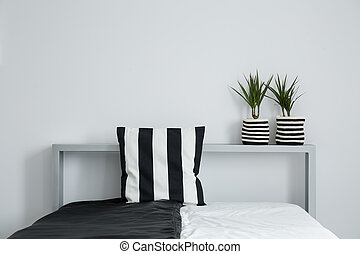 Striped pillow on black and white coverlet and two plants in...