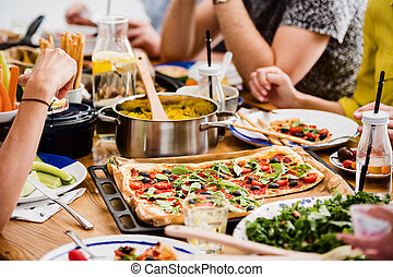 Communal table with fresh pizza millet groats healthy salad...