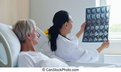 Pleasant female doctor showing x ray scan to her aged...