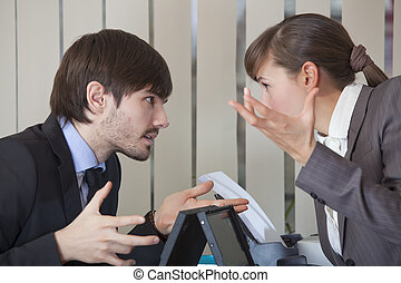 two office workers in conflict - frustrated man and woman...