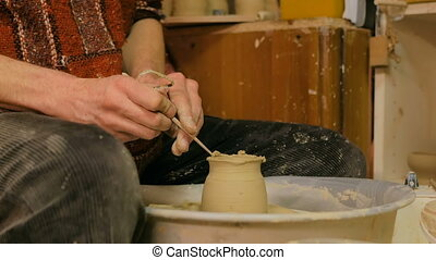 Professional potter carving mug with special tool in pottery...