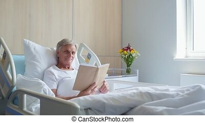 Pleasant old inpatient reading a book in his bed - Eternal...