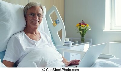 Positive aged man lying in the hospital bed with laptop - In...