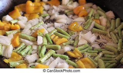 Asparagus beans in a frying pan with onions and carrots are...