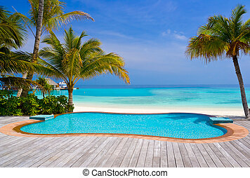 Pool on a tropical beach - vacation background