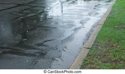 heavy rain drops falling on city street during downpour -...