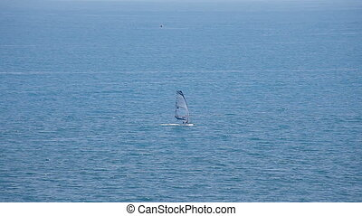 Windsurfer with a sailboat in the sea.