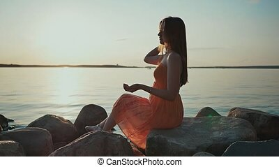 A young girl sits on rocks on the beach at sunset and throws stones. In the background of a boat with sails.