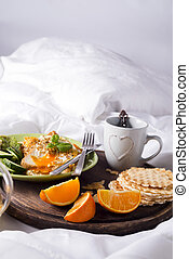 Fried eggs with toasts and tea in bed - A wooden tray with...
