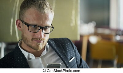 Trendy man looking gaze and holding a mobile phone. - Trendy...