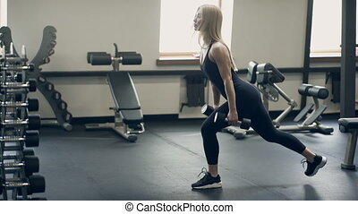 Beautiful woman does exercises squatting with lunges in...