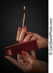 Woman hands ignite big matches for a cigar or fireplace -...