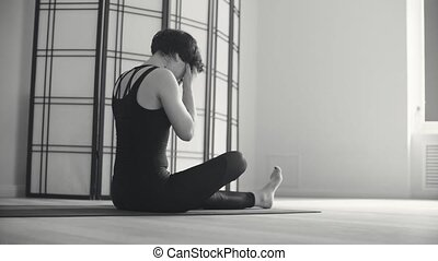 A young woman resting after yoga-asanas in the hall