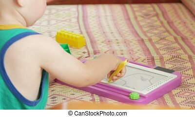 A nice boy of 2 years draws on a magnetic drawing board. He has great incomprehensible figures. The kid tries very hard