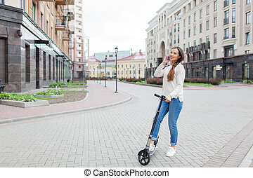 Beautiful young girl with long brown hair stopped while riding the scooter to talk to a friend on the phone on the background of the new residential quarter. She is dressed in a white sweater and blue jeans. Urban background