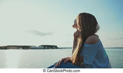 Pretty young girl sitting at the seashore watching the...
