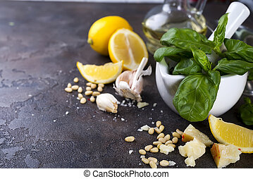 Ingredients for making pesto sauce on a black stone...
