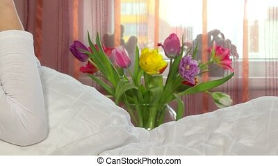 Bouquet of tulip flowers and happy girl talking with smart...