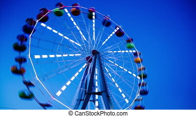 The night comes on the background of a Ferris wheel.