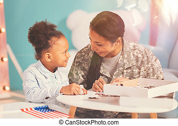Military mother and her daughter doing a jigsaw puzzle