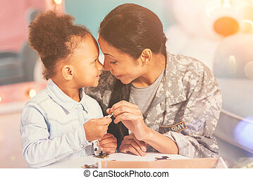Mother and daughter Eskimo-kissing while doing a puzzle -...