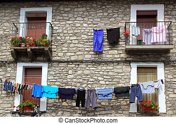 Clothes line hanging from stone wall houses in Spain