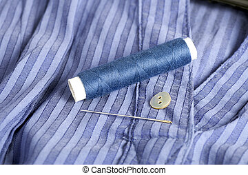 Mending - Blue shirt with button, thread and sewing needle...