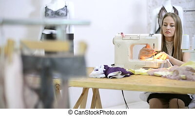 Sewer putting thread in sewing machine preparation in atelier