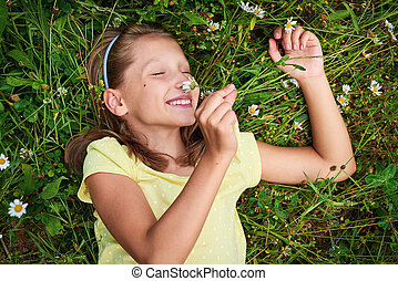 Happy girl lying in meadow between camomiles smelling the...