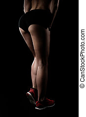 low section view of sportswoman posing in sportswear and...