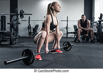 woman doing strength training with barbell while man sitting at gym
