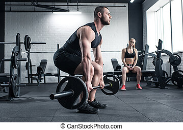 man doing strength training with barbell while woman sitting at gym
