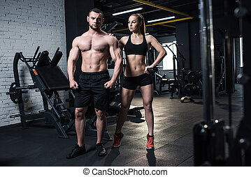 young fit couple in sportswear posing together at gym