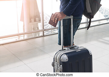 Close up of man hand holding passport and luggage suitcase at airport