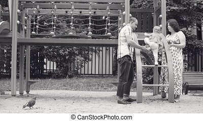 Little baby girl climbing on a ladder. Her daddy helping her